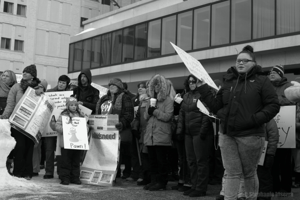 Protesters congregate at the Utica State Office Building.