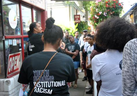 Aaron Dixon (far left) speaks with Freedom School students during the tour. (Photo: Celia Berk)