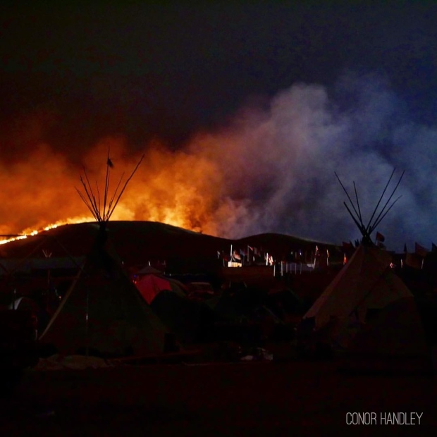 Fire on one side and the lights from DAPL construction and the police blockade on the other. No fire support came for over 7 hours. The fire was within a few hundred feet of camp just across the 1806 highway but the wind kept us safe and blew it in the other direction, towards the construction site.