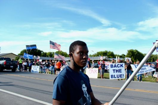 This young Utica Abolitionist holds the line, undeterred by the constant stream of death threats and racial slurs from the Trump and Tenney supporters. (Photo credit: Eamon Handzel)