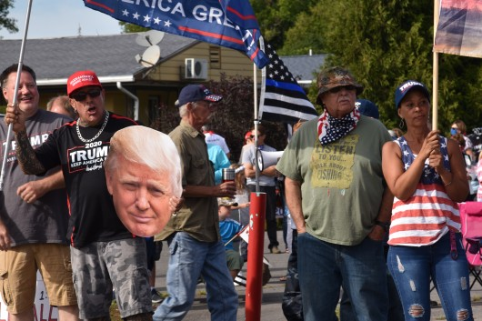 A Trump supporter holds a large decapitated head of the president. (Photo Credit: Love and Rage)
