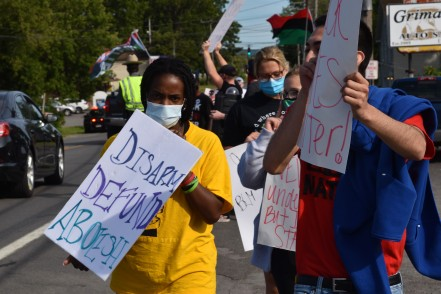 """""""Disarm, Defund, Abolish!"""" Utica Abolitionists and Black Lives Matter activists let their vision be known as they march at the counter-demonstration. (Photo Credit: Love and Rage)"""